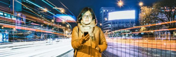 woman using her phone as lights pass