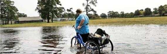 man with bike in flooded Orange, TX