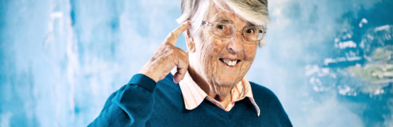 older woman points at head