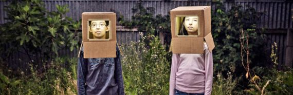 two kids wear cardboard robot costume hats
