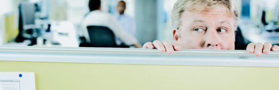 middle manager looking over cubicle wall