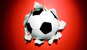 soccer ball busts through red paper