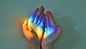 hands hold rainbow light