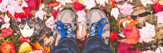 hiking boots from above with red maple leaves