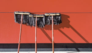 three mops against red wall (cellular cleaners & cancer concept)
