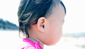 ear of toddler on the beach