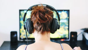 woman wears headphones while playing game