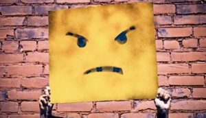 holding up angry face sign (negative feelings on surveys concept)