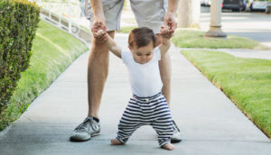 dad helps baby learning to walk