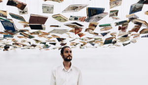 man stands under hanging books - poetry