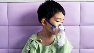 boy wearing breathing mask (cystic fibrosis concept)