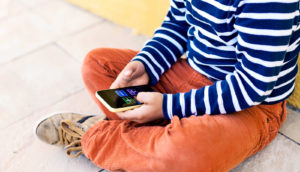 kid with phone (children and screens)