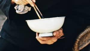 elderly woman holds white bowl