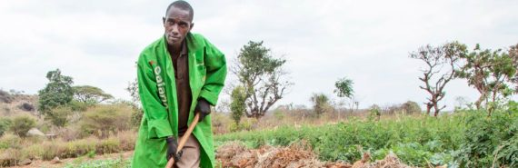 kenyan farmer wears green coat in field