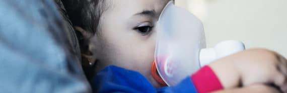 little girl using inhaler (asthma concept)