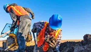 two muddy men look for mammoth bones