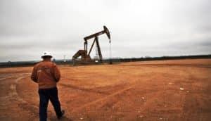 man walks toward pump in oil field