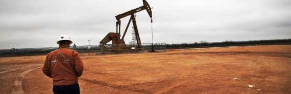 man walks toward pump in oil field