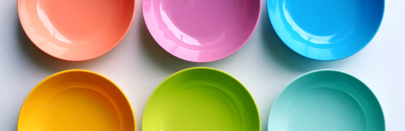 six rainbow-colored bowls on white