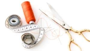 orange thread, measuring tape, gold scissors