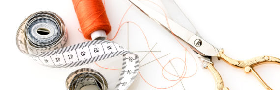 orange thread, measuring tape, gold scissors