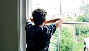 teen boy looking out window (sex offender registry concept)