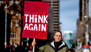 "man holds red ""think again"" sign"