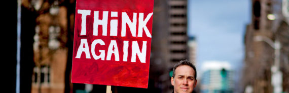 """man holds red """"think again"""" sign"""