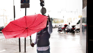 person fixes red umbrella on city street