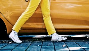 woman walking past car in yellow pants (Restless leg syndrome concept)