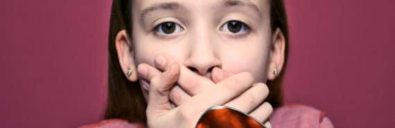 young girl refusing cough medicine