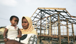 woman and baby in front of Banda Aceh reconstruction