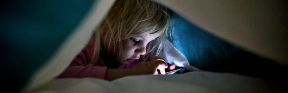 girl under covers with phone (sneaky media use)
