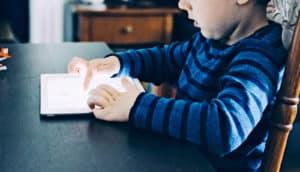 kid reading iPad (autism and bilingualism concept)