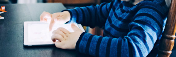 kid reading iPad (autism and bilingualism concept)