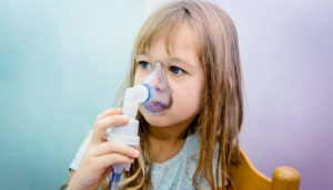 young girl with inhaler (asthma concept)