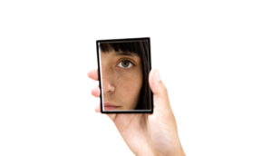 hand holds small mirror with woman's eye reflected