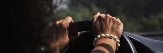 woman's hands on steering wheel