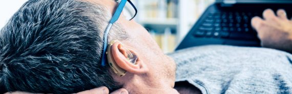 man with hearing aid (hearing loss concept)