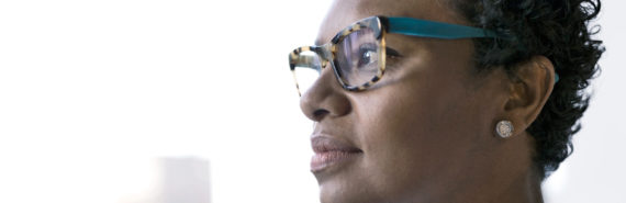 serious african-american woman looks out window