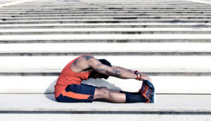 man stretching muscles on stairs