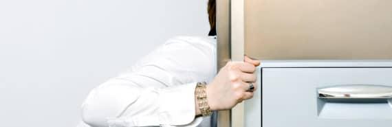 woman leans to open fridge