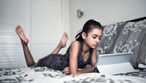 sad preteen girl uses laptop on bed