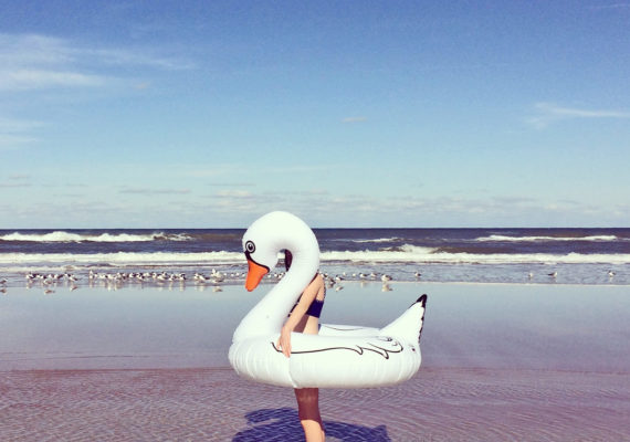 person in swan float at ocean (sunscreen and shinorine concept)