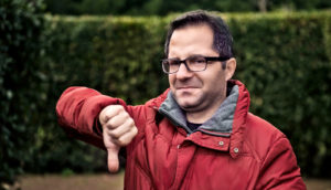 man in red parka gives thumbs down