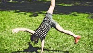 woman doing cartwheel on grass