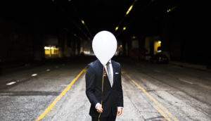 man in suit holds white helium balloon
