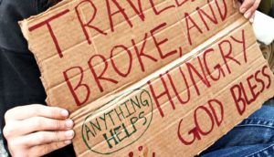 homeless young adult holding sign (food insecurity concept)