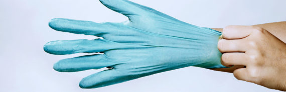 putting on medical glove (infectious disease specialists concept)