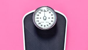 scale on pink (obesity paradox concept)
